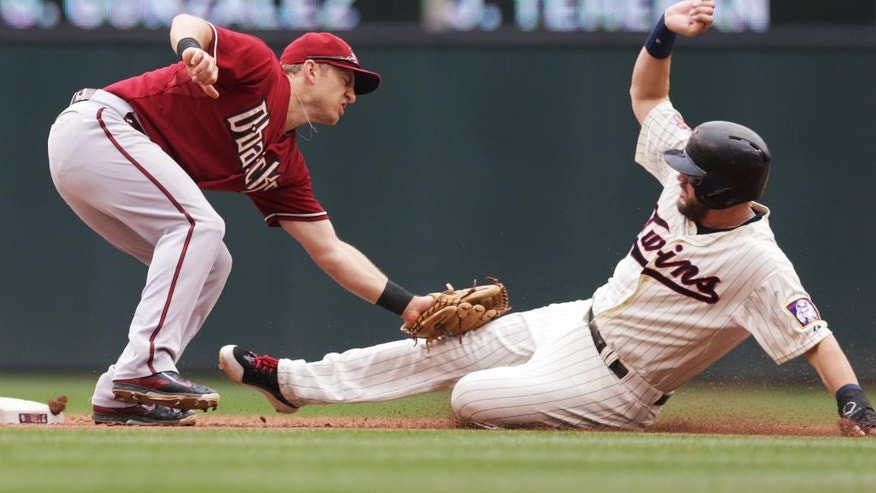 Arizona Diamondbacks second baseman Cliff Pennington, left, tag out Minnesota Twins' Trevor Plouffe as he attempted to steal second in the fifth inning of a baseball game, Wednesday, Sept. 24, 2014, in Minneapolis. (AP Photo/Jim Mone)