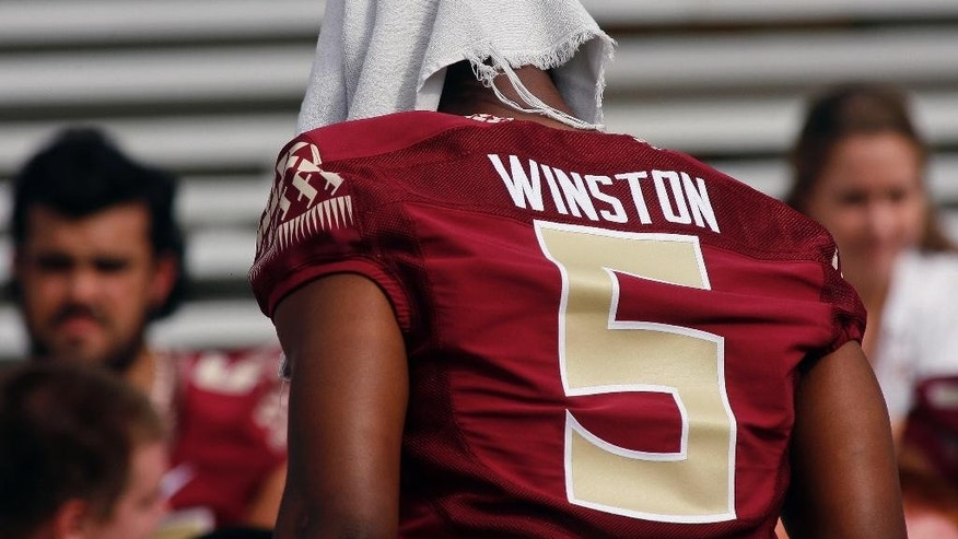 FILE - In this Aug. 10, 2014, file photo, Florida State quarterback Jameis Winston (5) has a towel on his head as he waits for a team photo during NCAA college football media day in Tallahassee, Fla. Attorneys for the woman who said Jameis Winston sexually assaulted her and an adviser for the Florida State quarterback's family confirm there were discussions about a potential settlement deal last year. They strongly disagree, however, on who initiated the talks. Attorney David Cornwell said in a Sept. 23 letter to Florida State that the woman's former lawyer Patricia Carroll demanded $7 million to settle her claim against Winston, the university and the Tallahassee Police Department. Baine Kerr, one of the lawyers for the woman, said in a statement emailed to The Associated Press that Cornwell sought the settlement. (AP Photo/Phil Sears, File)