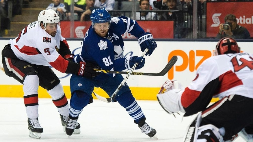 Toronto Maple Leafs forward Phil Kessel (81) drives to the net past Ottawa Senators defenseman Cody Ceci (5) as Senators goalie Robin Lehner, right, watches during the second period of an NHL preseason hockey game Wednesday, Sept. 24, 2014, in Toronto. (AP Photo/The Canadian Press, Nathan Denette)