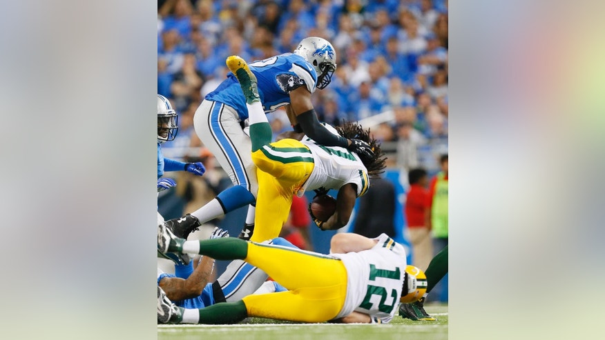 Detroit Lions defensive end Devin Taylor, top, stops Green Bay Packers running back Eddie Lacy, center, during the first half of an NFL football game in Detroit, Sunday, Sept. 21, 2014. (AP Photo/Paul Sancya)