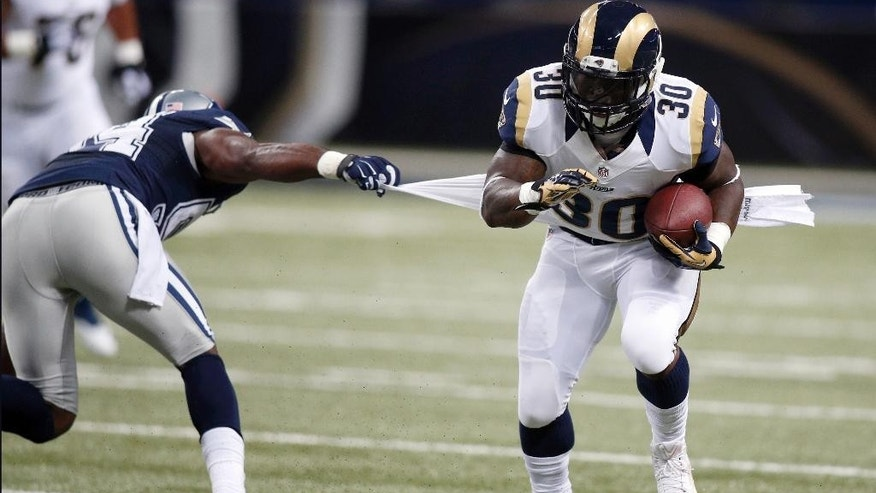 St. Louis Rams running back Zac Stacy, right, runs with the ball after catching a pass for a 14-yard gain as Dallas Cowboys linebacker Bruce Carter, left, defends during the first quarter of an NFL football game Sunday, Sept. 21, 2014, in St. Louis. (AP Photo/Scott Kane)