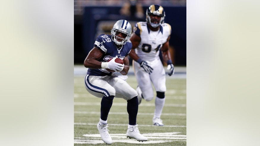 Dallas Cowboys running back DeMarco Murray, left, runs for a 14-yard gain as St. Louis Rams defensive end Robert Quinn defends during the second quarter of an NFL football game Sunday, Sept. 21, 2014, in St. Louis. (AP Photo/Scott Kane)