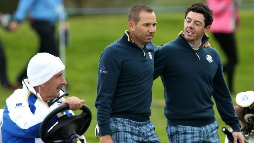 Europe's Rory McIlroy, right, and Sergio Garcia walk alongside team vice captain Sam Torrance in a golf buggy on the 15th fairway during a practice round ahead of the Ryder Cup golf tournament at Gleneagles, Scotland, Tuesday, Sept. 23, 2014. (AP Photo/Peter Morrison)