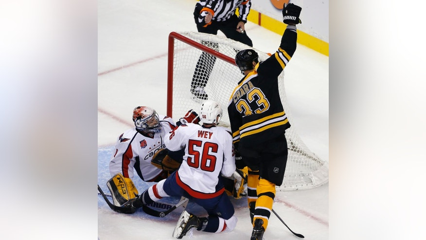 Boston Bruins defenseman Zdeno Chara celebrates his goal against Washington Capitals goalie Pheonix Copley as defenseman Patrick Wey (56) kneels next to them during the third period of an NHL preseason hockey game in Boston, Wednesday, Sept, 24, 2014. The Bruins won 2-0. (AP Photo/Elise Amendola)