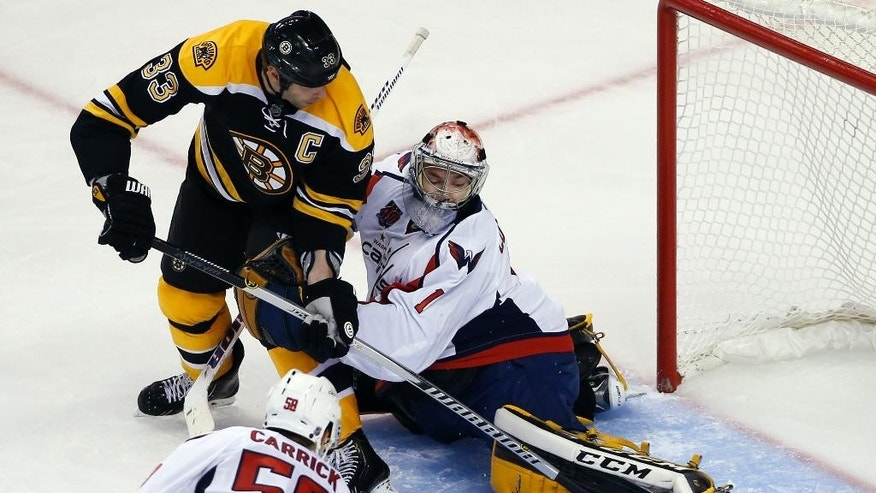 Boston Bruins defenseman Zdeno Chara puts pressure on Washington Capitals goalie Pheonix Copley, who kicks the puck away as defenseman Connor Carrick (58) watches during the third period of an NHL preseason hockey game in Boston, Wednesday, Sept, 24, 2014. The Bruins won 2-0. (AP Photo/Elise Amendola)