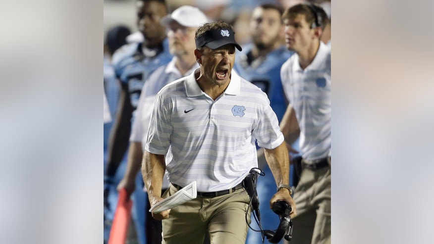 FILE - In this Aug. 30, 2014, file photo, North Carolina coach Larry Fedora yells during the second half of an NCAA college football game against Liberty in Chapel Hill, N.C. Three games into the season, North Carolina's defense is racking up big totals in all the wrong categories. Missed tackles. Blown assignments. And a bunch of points and yards allowed. (AP Photo/Gerry Broome, File)