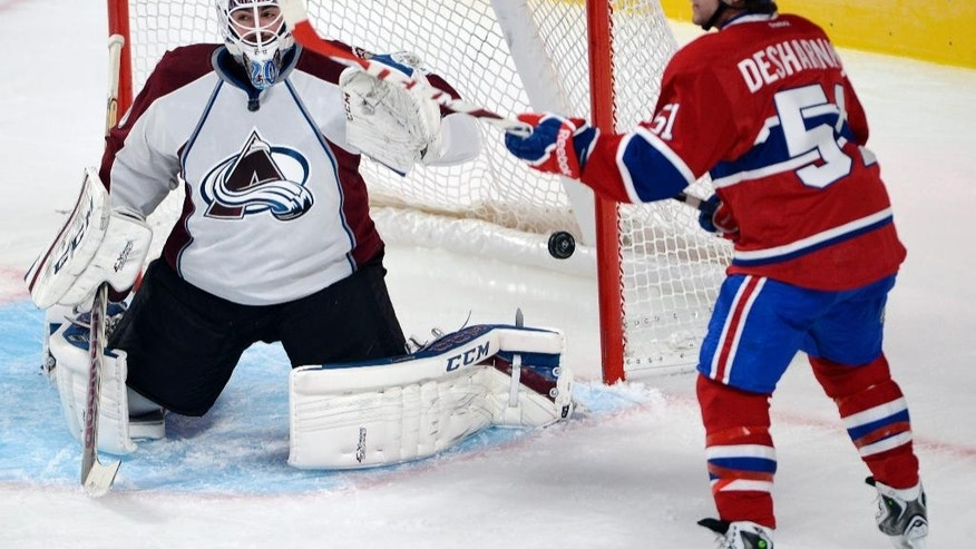 Colorado Avalanche goalie Reto Berra lets in the first goal as Montreal Canadiens center David Desharnais (51) watches during the second period of an NHL hockey preseason game Thursday, Sept. 25, 2014, in Montreal. (AP Photo/The Canadian Press, Ryan Remiorz)