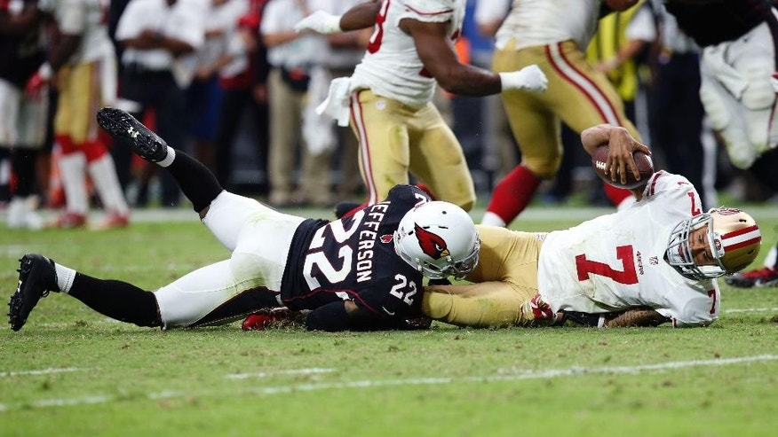 San Francisco 49ers quarterback Colin Kaepernick (7) is sacked by Arizona Cardinals free safety Tony Jefferson (22) during the second half of an NFL football game, Sunday, Sept. 21, 2014, in Glendale, Ariz. The Cardinals won 23-14. (AP Photo/Ross D. Franklin)