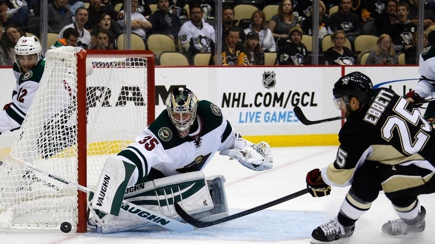 Minnesota Wild goalie Darcy Kuemper (35) blocks a shot by Pittsburgh Penguins' Andrew Ebbett (25) in the second period of an NHL preseason hockey game in Pittsburgh, Thursday, Sept. 25, 2014. (AP Photo/Gene J. Puskar)