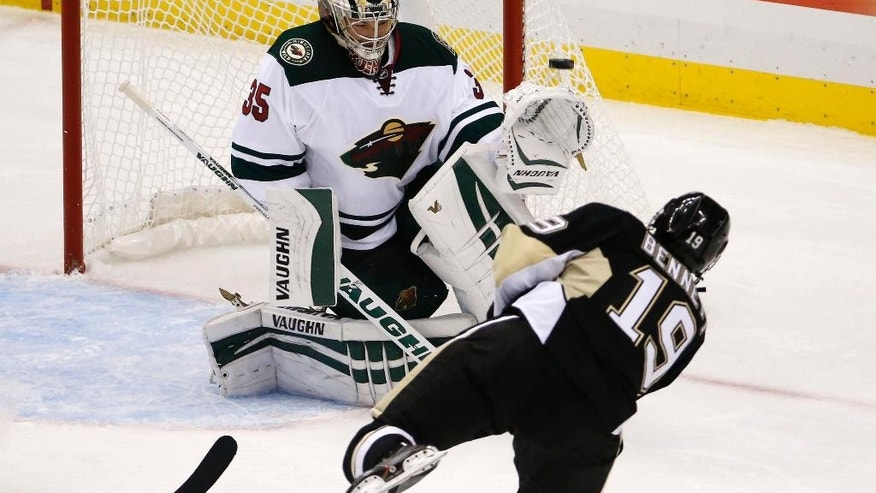 Minnesota Wild goalie Darcy Kuemper (35) blocks a shot by Pittsburgh Penguins' Beau Bennett (19) in the first period of an NHL preseason hockey game in Pittsburgh, Thursday, Sept. 25, 2014. (AP Photo/Gene J. Puskar)