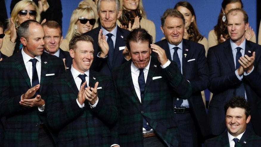 Phil Mickelson, center, salutes as he is announced as part of the US team during the opening ceremony for the Ryder Cup golf tournament at Gleneagles, Scotland, Thursday, Sept. 25, 2014. (AP Photo/Matt Dunham)