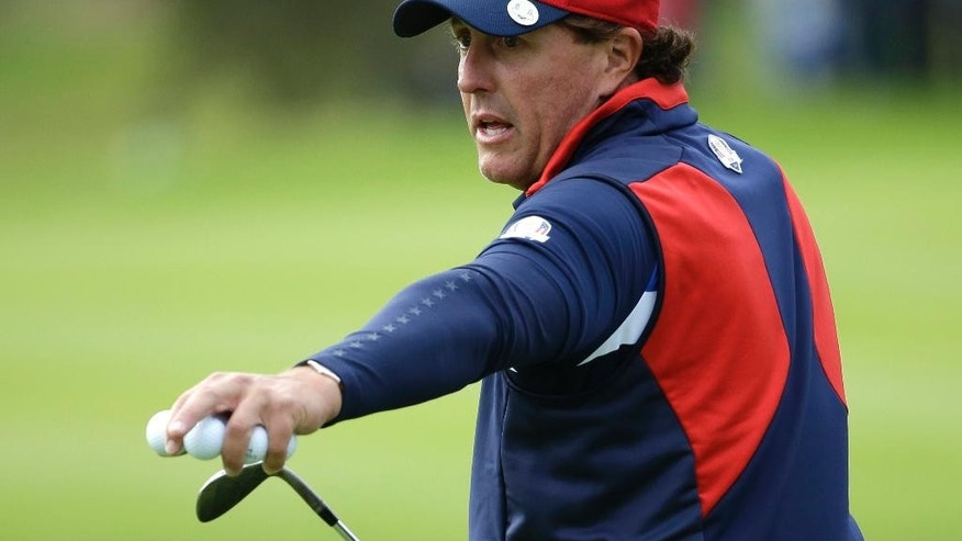Phil Mickelson of the US gestures as he walks off the 12th green after playing during a practice round ahead of the Ryder Cup golf tournament at Gleneagles, Scotland, Thursday, Sept. 25, 2014. (AP Photo/Matt Dunham)