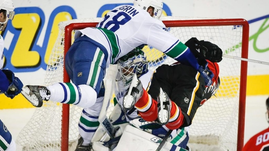 Vancouver Canucks' John Negrin, left, checks Calgary Flames' Sam Bennett, right, into goalie Joacim Eriksson during second-period NHL preseason hockey game action in Calgary, Alberta, Thursday, Sept. 25, 2014. (AP Photo/The Canadian Press, Jeff McIntosh)