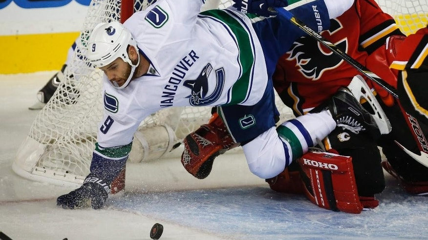 Vancouver Canucks' Zack Kassian, left, crashes over Calgary Flames goalie Jonas Hiller, from Switzerland, during first-period NHL preseason hockey game action in Calgary, Alberta, Thursday, Sept. 25, 2014. (AP Photo/The Canadian Press, Jeff McIntosh)