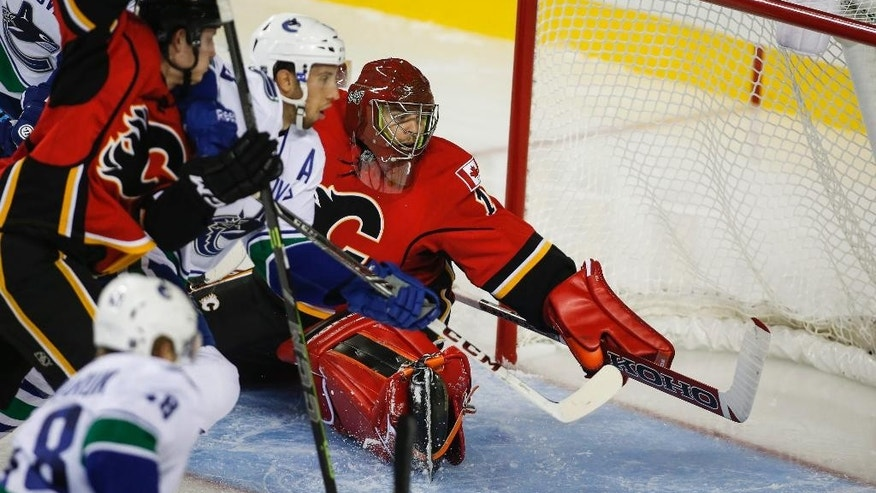 Vancouver Canucks' Nick Bonino, center, chases the puck past Calgary Flames goalie Jonas Hiller, right, from Switzerland, during second-period NHL preseason hockey game action in Calgary, Alberta, Thursday, Sept. 25, 2014. (AP Photo/The Canadian Press, Jeff McIntosh)