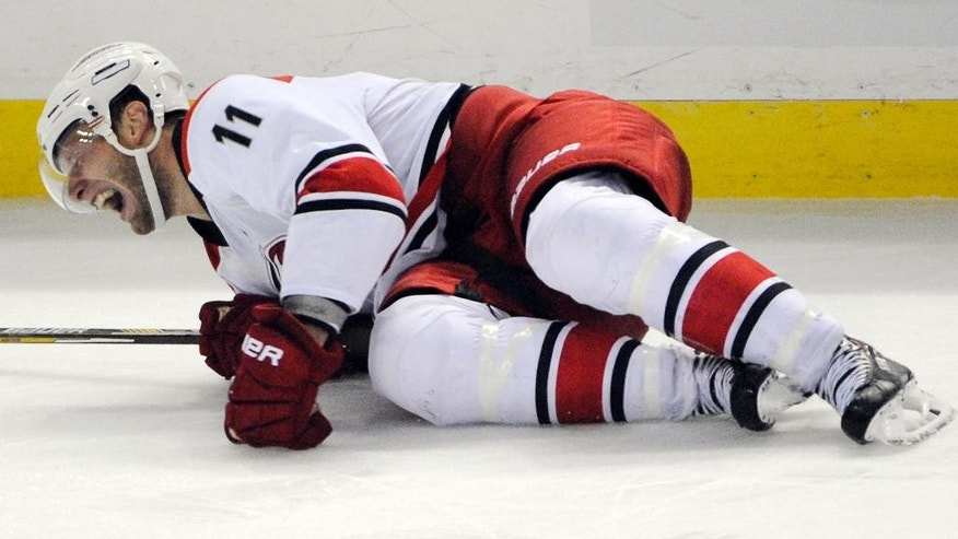 Carolina Hurricanes center Jordan Staal grimaces as he lays on the ice during the third period of an NHL hockey preseason game against the Buffalo Sabres, Tuesday, Sept. 23, 2014, in Buffalo, N.Y. Staal was walking on crutches and will require further tests to determine the severity of a right leg injury sustained. (AP Photo/Gary Wiepert)