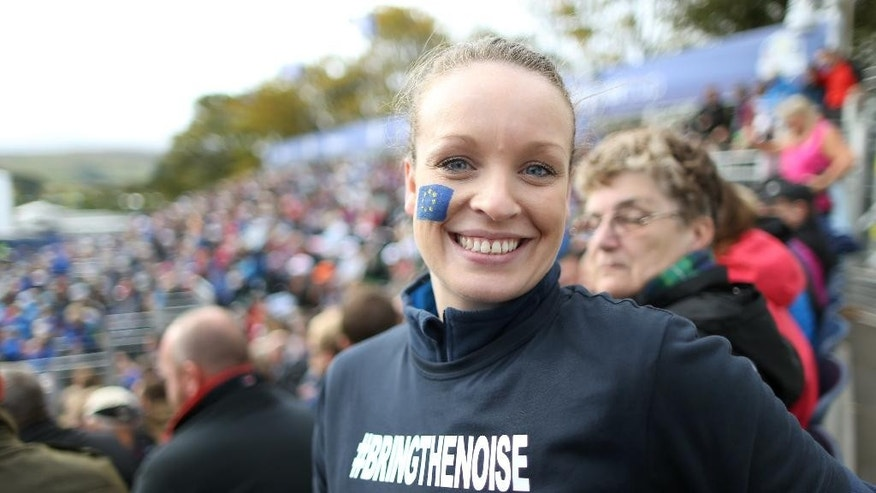 A fan supporting the European team smiles from the stands overlooking the 1st hole ahead of the Ryder Cup golf tournament, at Gleneagles, Scotland, Thursday, Sept. 25, 2014. (AP Photo/Peter Morrison)