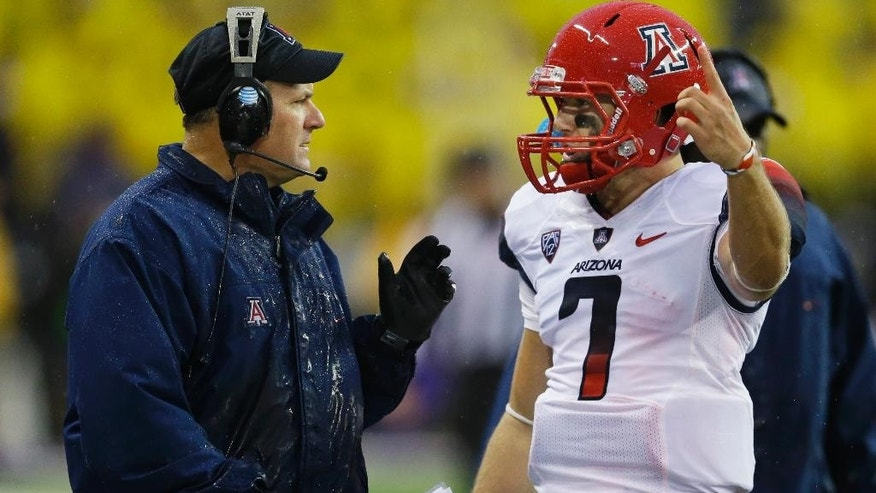 FILE - In this Sept. 28, 2013, file photo, Arizona head coach Rich Rodriguez, left, talks quarterback B.J. Denker during a time out in an NCAA college football game against Washington in Seattle. The zone read has become one of the most popular offenses in college football, a multidimensional shotgun-based option system that requires impeccable timing and often leaves defenses guessing and grasping. Rodriguez ran the offense in relative obscurity while at Glenville State. As Rodriguez moved onto jobs at West Virginia, Michigan and now Arizona, the zone read spread across college football. (AP Photo/Ted S. Warren, File)