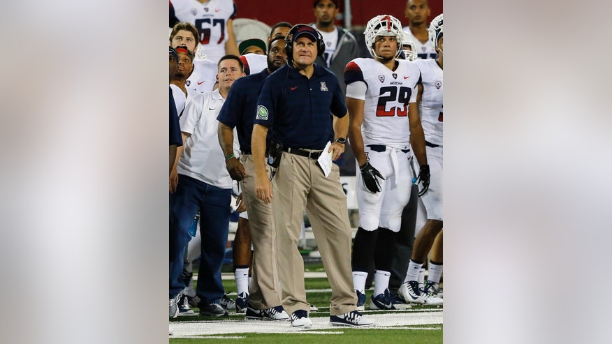 FILE - In this Sept. 20, 2014, file photo, Arizona head coach Rich Rodriguez watches from the sideline during the second half of an NCAA college football game against California in Tucson, Ariz. The zone read has become one of the most popular offenses in college football, a multidimensional shotgun-based option system that requires impeccable timing and often leaves defenses guessing and grasping. Rodriguez ran the offense in relative obscurity while at Glenville State. As Rodriguez moved onto jobs at West Virginia, Michigan and now Arizona, the zone read spread across college football. (AP Photo/Rick Scuteri, File)