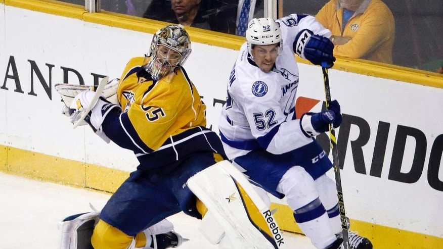 Nashville Predators goalie Pekka Rinne (35) tries to control the puck behind the net along with Tampa Bay Lightning right wing Jerome Samson (52) in the second period of a preseason NHL hockey game Thursday, Sept. 25, 2014, in Nashville, Tenn. (AP Photo/Mark Humphrey)