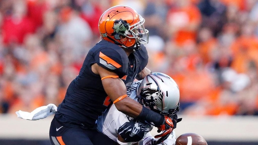 Oklahoma State cornerback Ashton Lampkin, left, breaks up a pass intended for Texas Tech wide receiver Reginald Davis, right, in the first quarter of an NCAA college football game in Stillwater, Okla., Thursday, Sept. 25, 2014. (AP Photo/Sue Ogrocki)