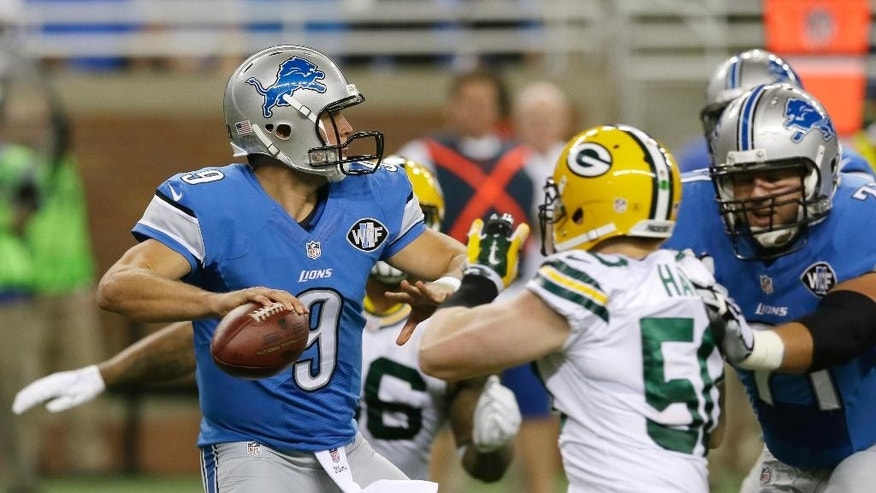 Detroit Lions quarterback Matthew Stafford, under pressure from Green Bay Packers inside linebacker A.J. Hawk, looks downfield during the first half of an NFL football game in Detroit, Sunday, Sept. 21, 2014. (AP Photo/Carlos Osorio)