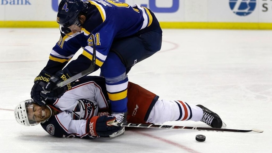 Columbus Blue Jackets' Jerry D'Amigo, bottom, is knocked to the ice by St. Louis Blues right wing Vladimir Tarasenko, of Russia, during the second period of a preseason NHL hockey game Thursday, Sept. 25, 2014, in St. Louis. (AP Photo/Jeff Roberson)