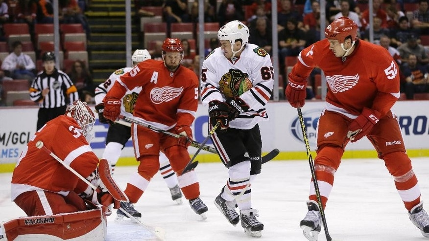 Chicago Blackhawks center Andrew Shaw (65) shoots on Detroit Red Wings goalie Jimmy Howard (35) during the first period of an NHL hockey game in Detroit, Thursday, Sept. 25, 2014. (AP Photo/Carlos Osorio)