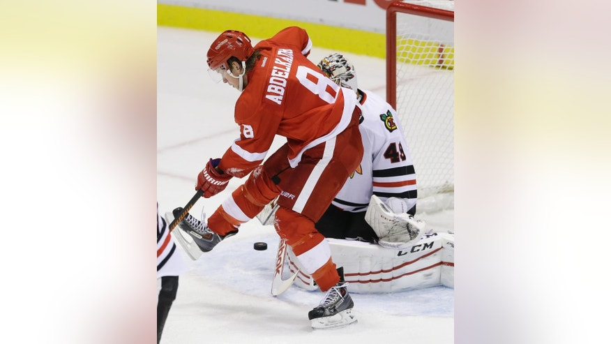 Detroit Red Wings left wing Justin Abdelkader (8) jumps in front of Chicago Blackhawks goalie Michael Leighton (49) as Leighton deflects a shot during the second period of an NHL hockey game in Detroit, Thursday, Sept. 25, 2014. (AP Photo/Carlos Osorio)