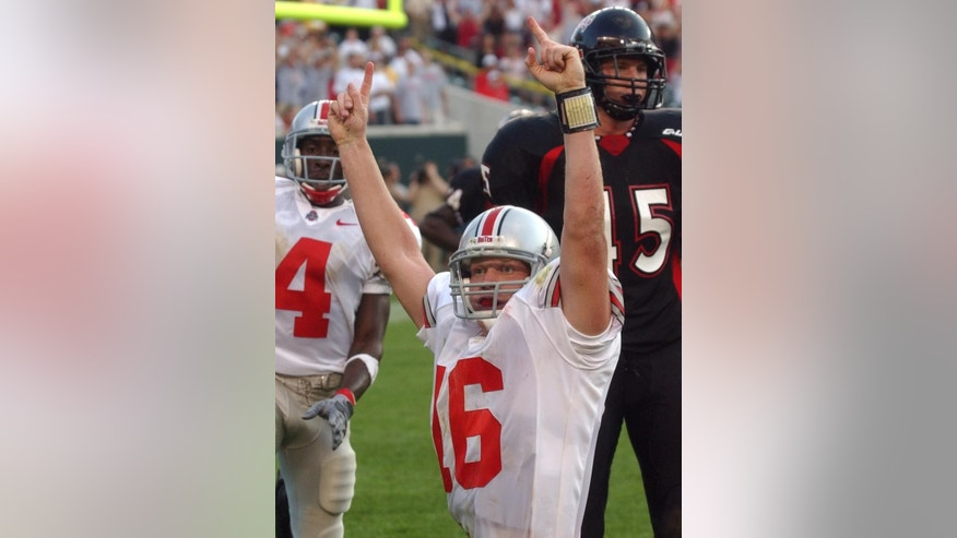 FILE - In this Sept. 21, 2002 file photo, Ohio State quarterback Craig Krenzel (16) celebrates after scoring on a six-yard run in the fourth quarter to beat Cincinnati 23-19, in Cincinnati. Ohio State has won the last 39 meetings with in-state teams, dating to a 7-7 tie with the College of Wooster in 1924. With the Cincinnati Bearcats playing the 22nd-ranked Buckeyes on Saturday, Sept. 27, 2014,  no one associated with Ohio State _ players, coaches or fans _ wants to think what the fallout would be if an in-state opponent were to finally upset them. (AP Photo/Al Behrman, File)