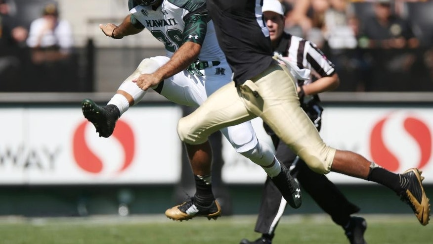 Hawaii punter Scott Harding, left, gets off punt as Colorado special teams player Evan White covers in the third quarter of Colorado's 21-12 victory in an NCAA college football game in Boulder, Colo., on Saturday, Sept. 20, 2014. (AP Photo/David Zalubowski)