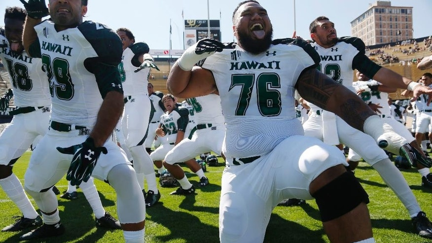 Hawaii punter/wide receiver Scott Harding, left, joins offensive lineman Dave Lefotu in leading teammates in the team's traditional ha'ka before facing Colorado in the first quarter of an NCAA college football game in Boulder, Colo., Saturday, Sept. 20, 2014. (AP Photo/David Zalubowski)