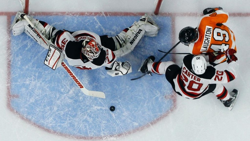 Philadelphia Flyers' Scott Laughton (49) scores a goal past New Jersey Devils' Cory Schneider (35) as Ryan Carter (20) defends during the second period of a preseason NHL hockey game, Thursday, Sept. 25, 2014, in Philadelphia. (AP Photo/Matt Slocum)
