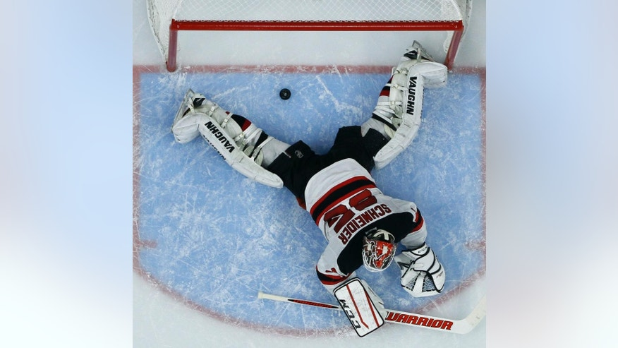 New Jersey Devils' Cory Schneider cannot stop a goal by Philadelphia Flyers' Scott Laughton that slid underneath him during the second period of a preseason NHL hockey game, Thursday, Sept. 25, 2014, in Philadelphia. (AP Photo/Matt Slocum)