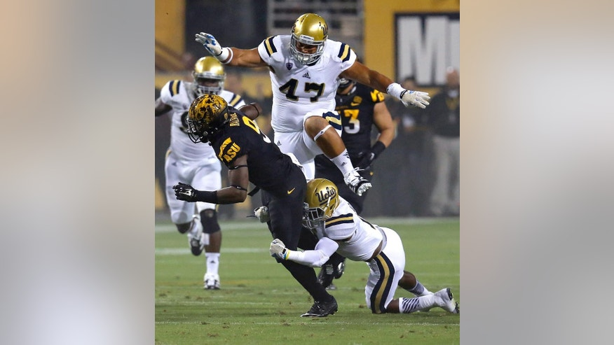 Arizona State running back Kalen Ballage is tackled by UCLA defensive back Ishmael Adams, right, as defensive lineman Eddie Vanderdoes (47) pursues during the first half of an NCAA college football game, Thursday, Sept. 25, 2014, in Tempe, Ariz. (AP Photo/Rick Scuteri)