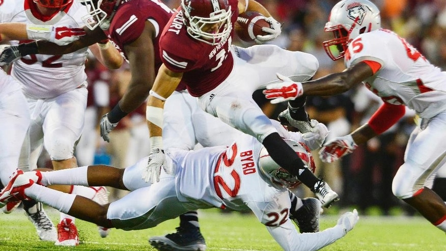 New Mexico State Aggie running back Brandon Betancourt leaps over New Mexico's Lobo Markel Byrd during the first half of play at Aggie Memorial Stadium on Saturday, Sept. 20, 2014, in Las Cruces New Mexico.  The Lobos won 38-35. (AP Photo/The Las Cruces Sun-News, Carlos Javier Sanchez)