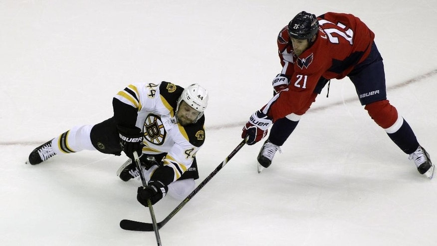 Boston Bruins' Dennis Seidenberg (44), of Germany, moves the puck as Washington Capitals' Brooks Laich (21) defends during the first period of a preseason hockey game, Friday, Sept. 26, 2014, in Washington. (AP Photo/Luis M. Alvarez)