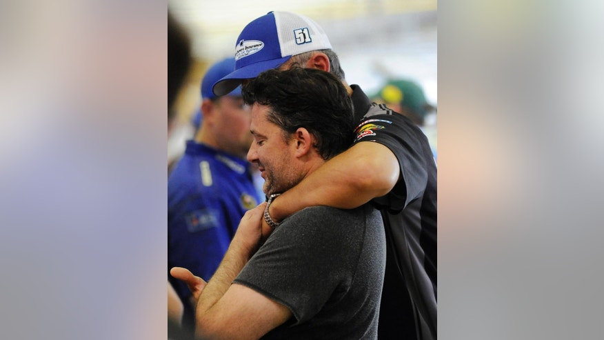 """FILE - In this Aug. 30, 2014, file photo, Tony Stewart gets a hug from former crew chief Steve Addington in the garage during practice for the NASCAR Sprint Cup series auto race at Atlanta Motor Speedway in Hampton, Ga. Stewart says that the crash that killed 20-year-old Kevin Ward Jr. on a dirt track in upstate New York was """"100 percent"""" an accident. Stewart spoke to The Associated Press from his home in Huntersville, N.C. It was his first interview since a grand jury decided against charging the NASCAR star in Ward's death. Stewart could still face a civil lawsuit. (AP Photo/David Tulis, File)"""