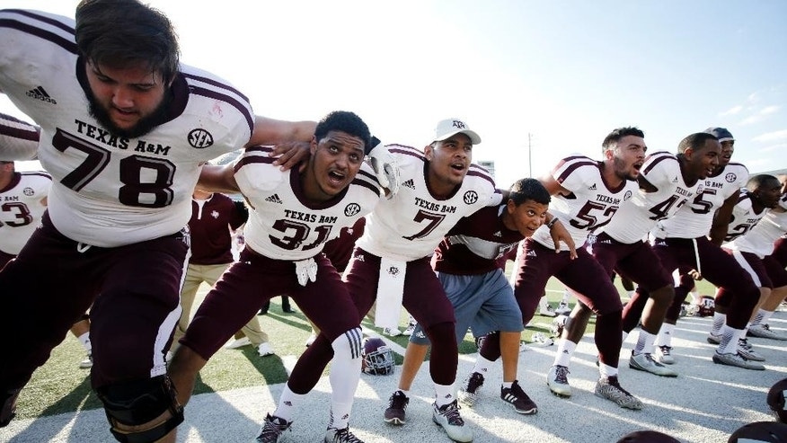 Texas A&M 's Garrett Gramling (78), Howard Matthews (31), Kenny Hill (7), Brett Wade (52) and others sing the Aggie War Hymn song after their NCAA college football game against SMU, Saturday, Sept. 20, 2014, in Dallas. Texas A&M won 58-6. (AP Photo/Tony Gutierrez)