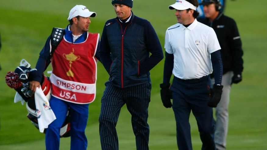 Webb Simpson of the US, center, walks along the 1st fairway with his caddie Paul Tesori, left, and Bubba Watson, right, during the fourball match on the first day of the Ryder Cup golf tournament, at Gleneagles, Scotland, Friday, Sept. 26, 2014. (AP Photo/Alastair Grant)