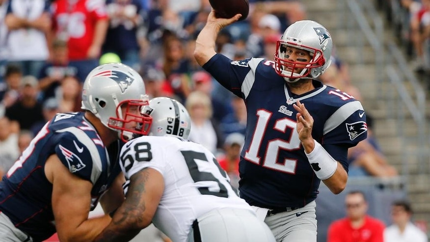 New England Patriots quarterback Tom Brady looks for a receiver over Oakland Raiders defensive end LaMarr Woodley (58) in the first half of an NFL football game, Sunday, Sept. 21, 2014, in Foxborough, Mass. (AP Photo/Elise Amendola)
