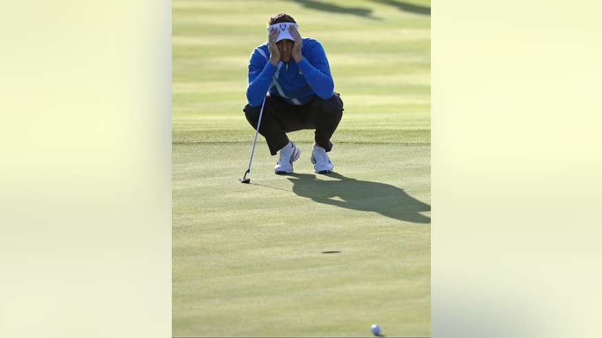 Europe's Ian Poulter lines up a putt on the 3rd green during the fourball match on the first day of the Ryder Cup golf tournament, at Gleneagles, Scotland, Friday, Sept. 26, 2014. (AP Photo/Scott Heppell)