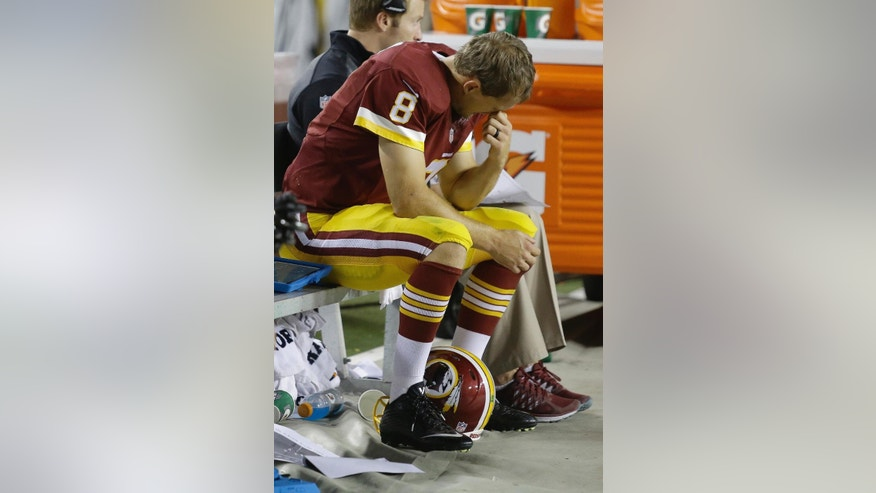 Washington Redskins quarterback Kirk Cousins (8) sits on the bench after this third interception, during the second half of an NFL football game against the New York Giants in Landover, Md., Thursday, Sept. 25, 2014. (AP Photo/Patrick Semansky)