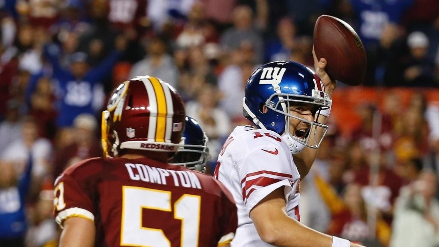 New York Giants quarterback Eli Manning (10) celebrates his touchdown during the second half of an NFL football game against the Washington Redskins in Landover, Md., Thursday, Sept. 25, 2014. (AP Photo/Alex Brandon)
