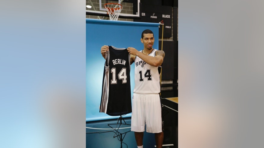 San Antonio Spurs' Danny Green holds a jersey to represent the team's first preseason game to be played in Berlin during NBA basketball media day at the team's practice facility, Friday, Sept. 26, 2014, in San Antonio. Green has changed his jersey number from 4 to 14. He wore No. 14 while in college at North Carolina. (AP Photo/Eric Gay)