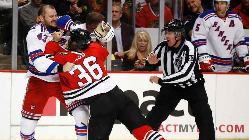 New York Rangers center Nick Tarnasky (43) and Chicago Blackhawks center Cody Bass (36) fight as linesman Andy McElman looks on during the first period of a preseason NHL hockey game on Friday, Sept. 26, 2014, in Chicago. (AP Photo/Andrew A. Nelles)