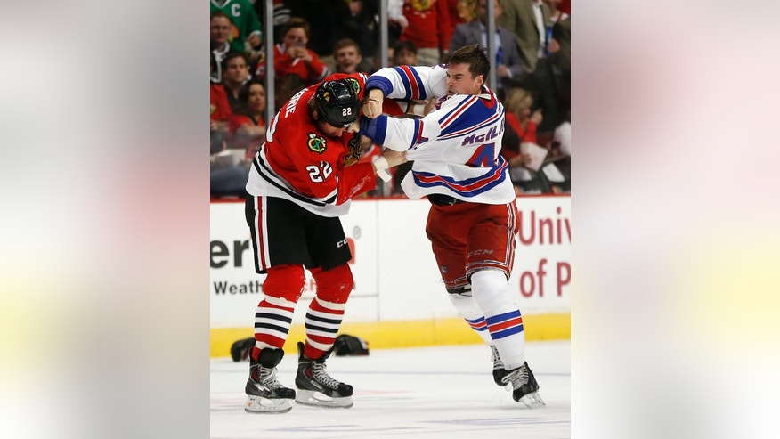 Chicago Blackhawks left wing Pierre-Cedric Labrie (22) and New York Rangers defenseman Dylan McIlrath (42) fight during the second period of a preseason NHL hockey game on Friday, Sept. 26, 2014, in Chicago. (AP Photo/Andrew A. Nelles)