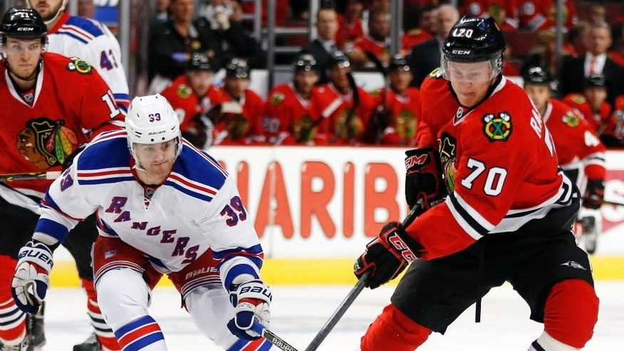 Chicago Blackhawks center Dennis Rasmussen (70) advances past New York Rangers right wing Ryan Haggerty (39) during the first period of a preseason NHL hockey game on Friday, Sept. 26, 2014, in Chicago. (AP Photo/Andrew A. Nelles)