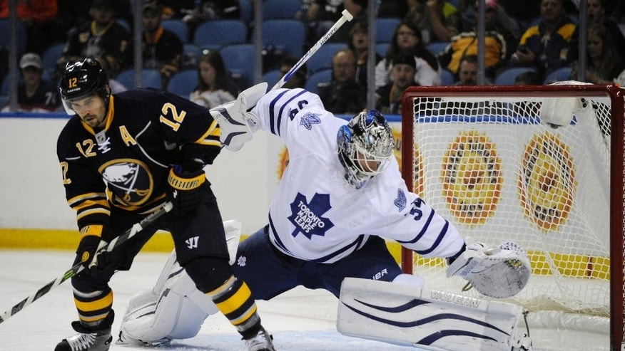 Buffalo Sabres right winger Brian Gionta (12) deflects the puck on goal as Toronto Maple Leafs goaltender James Reimer (34) defends during the first period of an NHL hockey preseason game, Friday, Sept. 26, 2014, in Buffalo, N.Y. (AP Photo/Gary Wiepert)