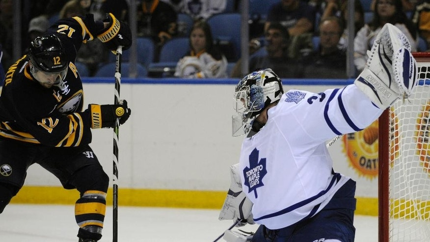 Buffalo Sabres right winger Brian Gionta (12) shoots the puck at Toronto Maple Leafs goaltender James Reimer (34) during the first period of an NHL hockey preseason game, Friday, Sept. 26, 2014, in Buffalo, N.Y. (AP Photo/Gary Wiepert)